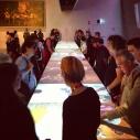Molta gente intorno al tavolo interattivo del padiglione Santa Sede